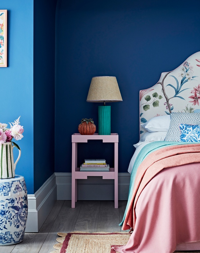 Bright blue wall with pink bedding in bedroom