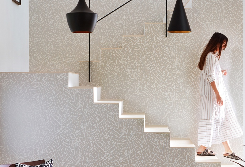 White patterned wallpaper with woman walking downstairs