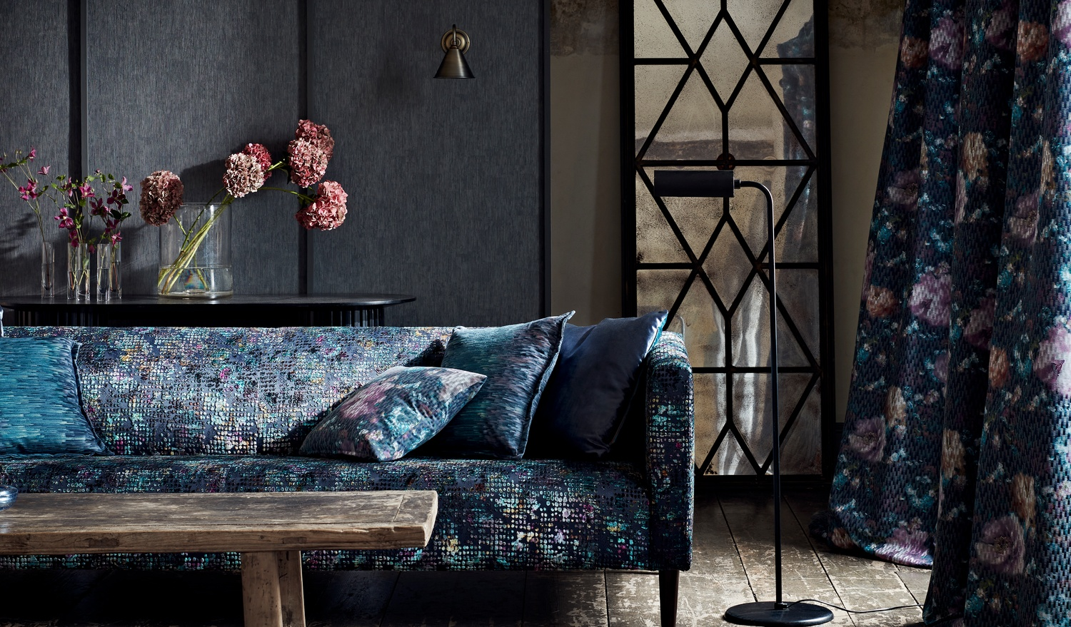Deep blue and purple sofa with cushions and curtain