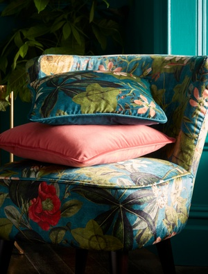 Green and pink floral cushions on chair