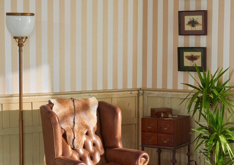 Striped pink and white wallpaper with leather chair