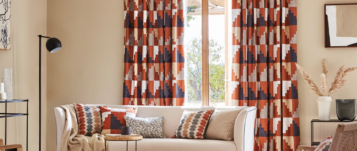 Harlequin Mirador orange and navy blue fabric curtains and cushions in lounge